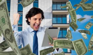 A happy businessman looking at a tablet with dollar bills raining on him